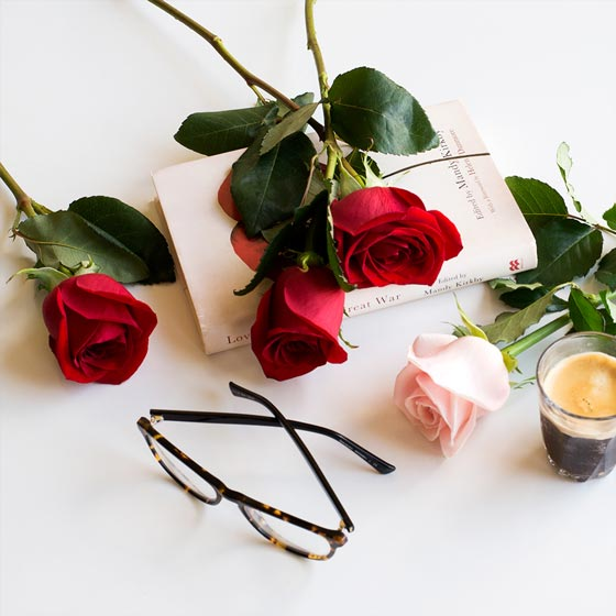 red roses with book reading glasses and coffee