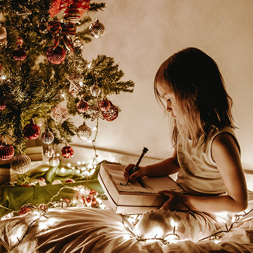 girl writing christmas wish list next to christmas tree
