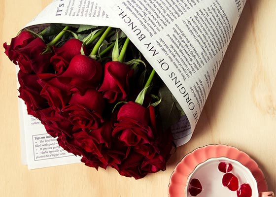 Fresh red roses in a newspaper wrap.