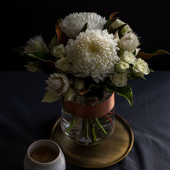 moody shot of white blushing bride flower arrangement on table with a coffee