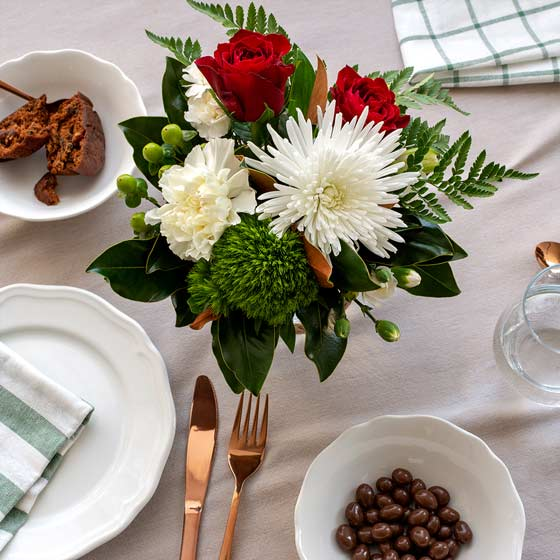 red white and green flower arrangement on table with plates and napkins