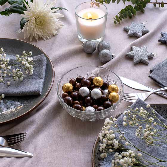 Christmas table with chocolates plates and white flowers