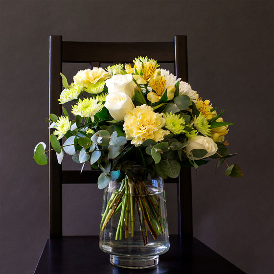 yellow easter flowers in vase on chair