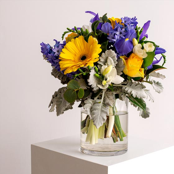 purple and yellow flower arrangement in glass vase