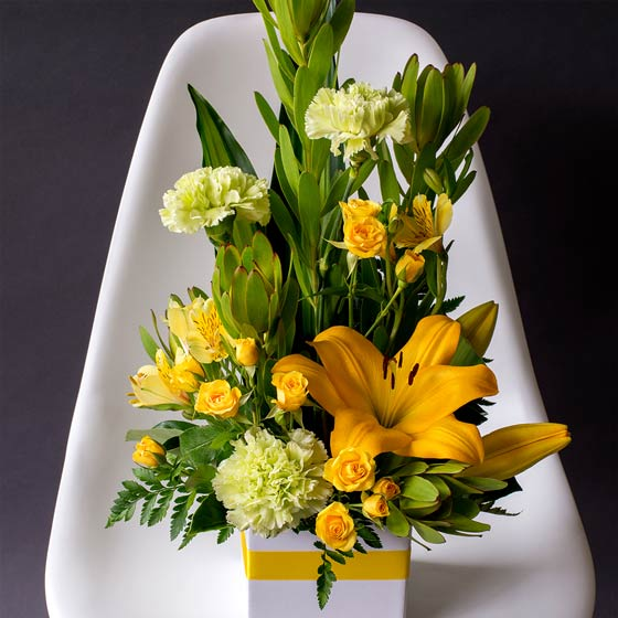 flower arrangement with yellow lily and green chrysanthemums in white box on chair