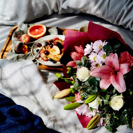 mother's day flower bouquet on bed with breakfast