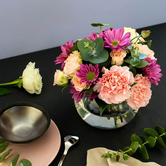 mother's day flowers in fishbowl vase on table
