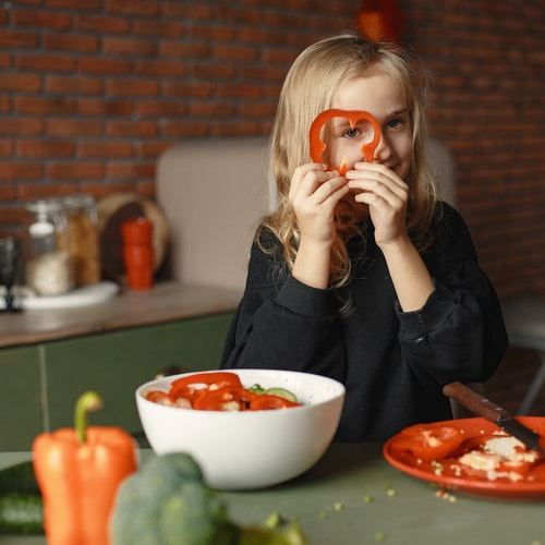 girl playing with capsicum and vegetables