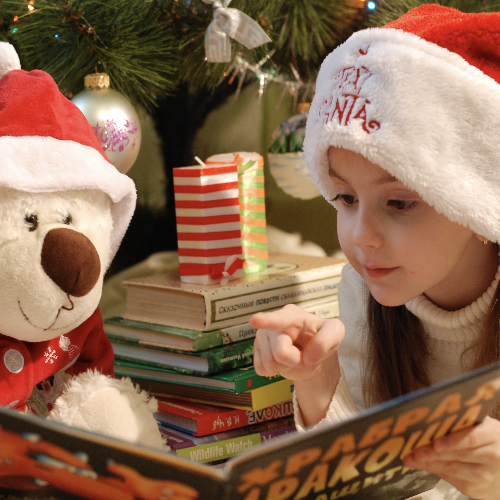 girl reading in front of christmas tree