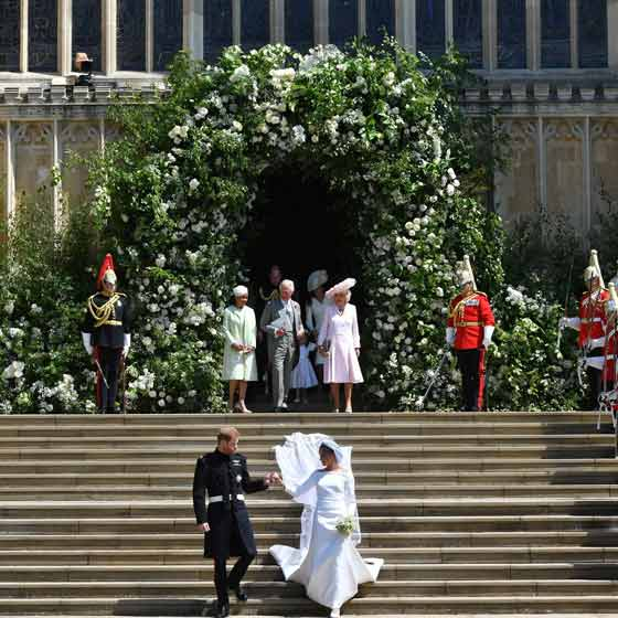 royal wedding prince harry and maghan markle on steps with flower arch behind