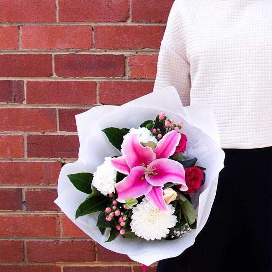 girl holding pink lily bouquet