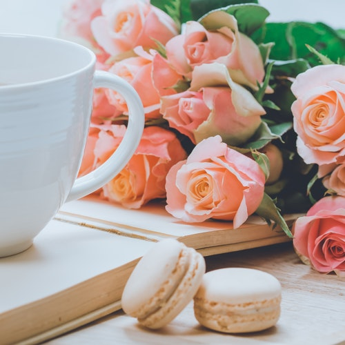 bouquet of pink roses on a table with a coffee mug and macaroons