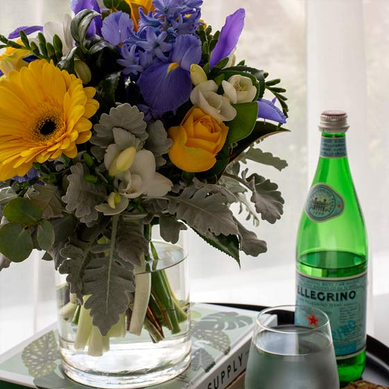 purple and yellow flowers in glass vase on table
