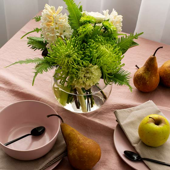 green floral arrangement on table with pink linen