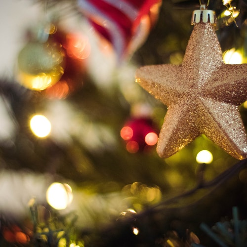 gold star christmas decoration hanging on tree