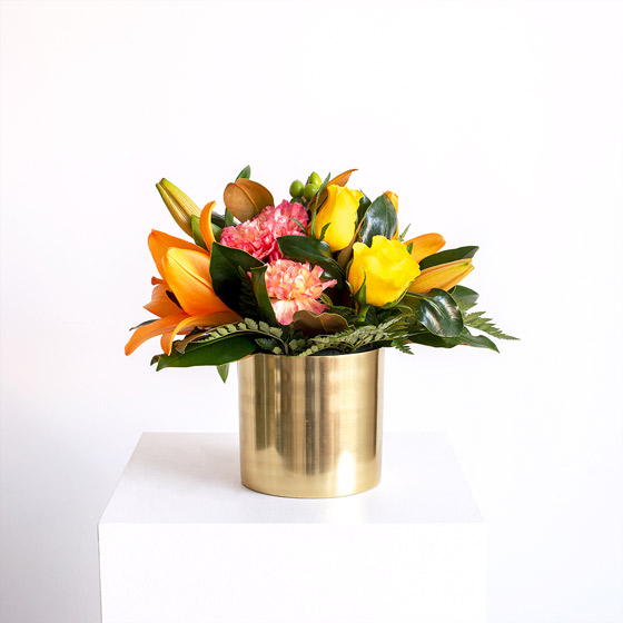 orange pink and yellow flowers in gold vase