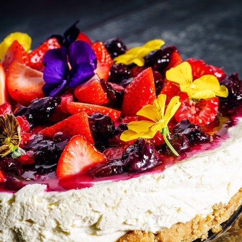 white pavlova cake with strawberries, raspberries and pansies as a garnish
