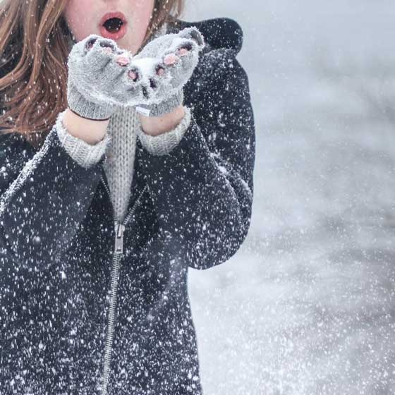 girl in snow with gloves on