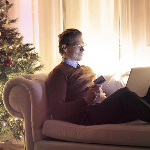 Man on laptop in front of Christmas tree video calling on couch