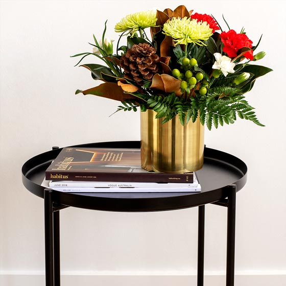 christmas flower arrangement with pinecone in gold vase on table